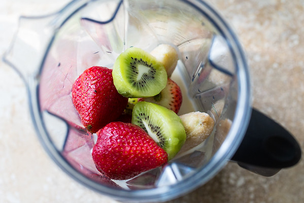 Strawberries, kiwi, banana, and milk for smoothie