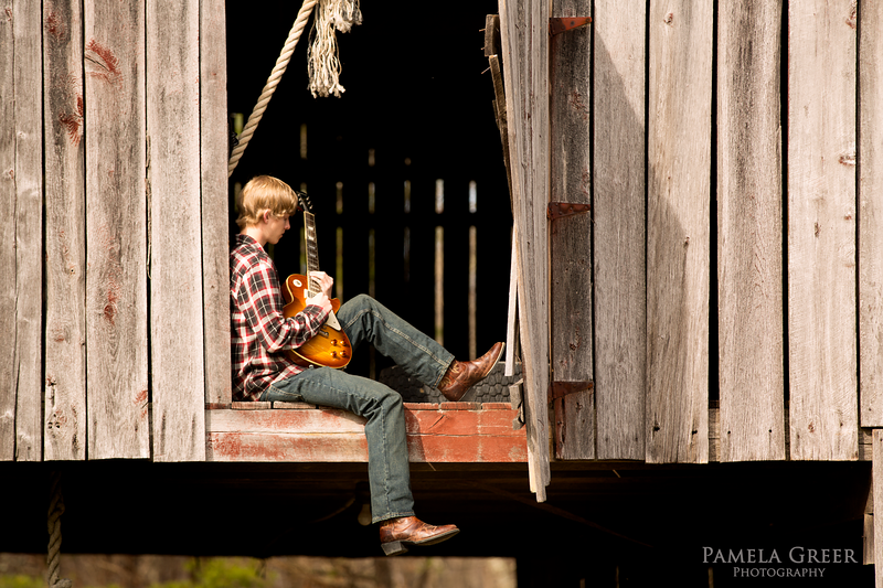 Pamela Greer Photography senior boy in barn playing guitar