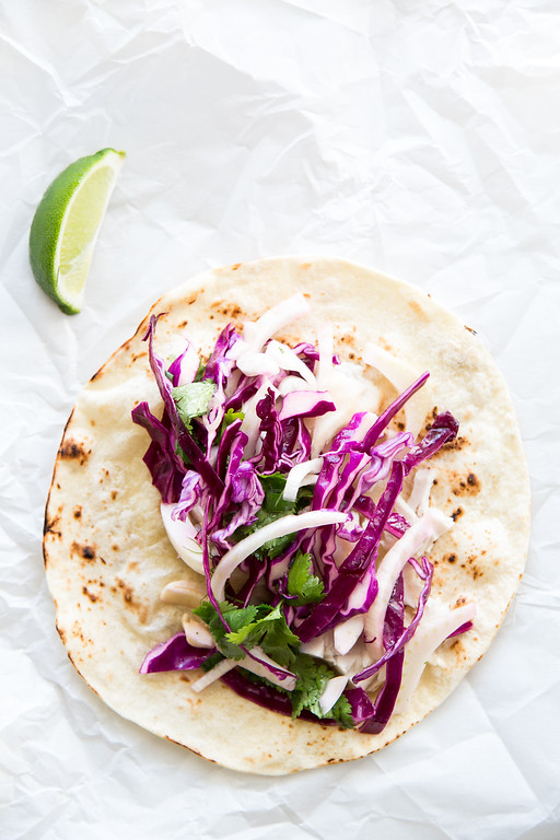 Fish tacos with fennel slaw resting on a white paper with a lime wedge